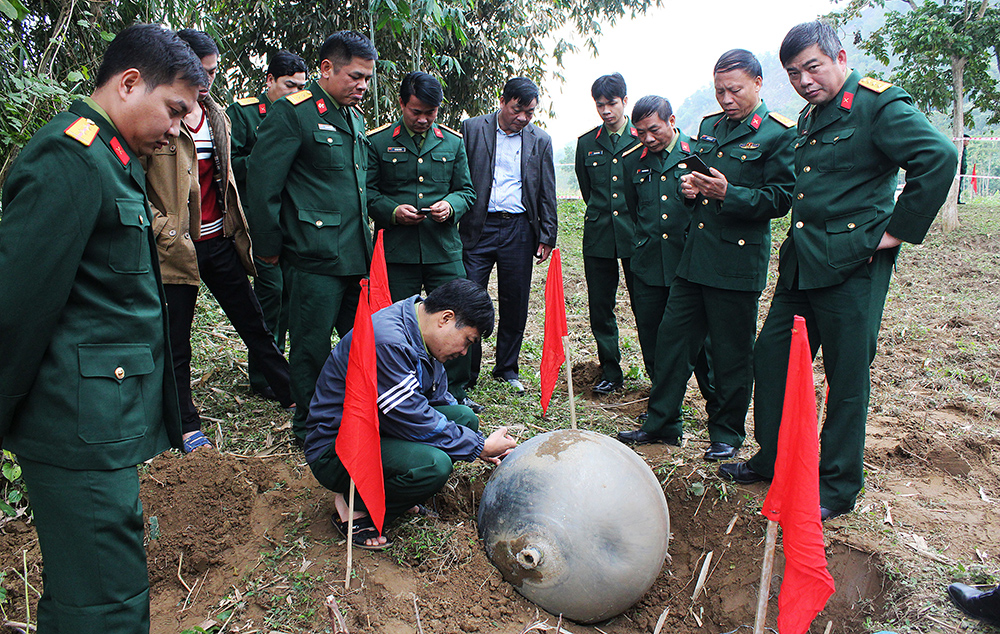 This picture taken on January 2, 2016 shows a group of military officers inspecting a metal ball which landed in the northern province of Tuyen Quang.  Vietnam's military is investigating three large metal balls, believed to be space junk, which landed in the country's remote north over the last week, a senior army official said on January 8, 2016.  AFP PHOTO  / AFP / STR